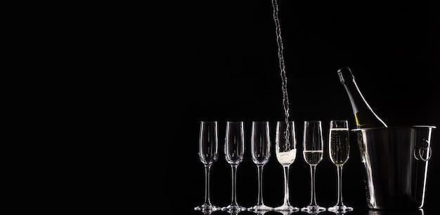 Servizio di catering. sagoma con bottiglia di champagne in un secchio e bicchieri. versare champagne.