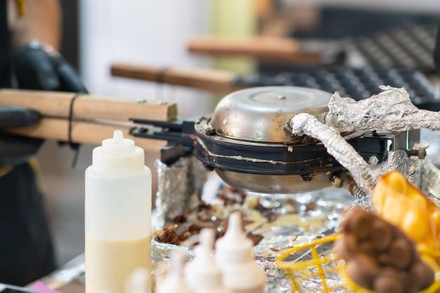 Tavolo da catering con piastra elettrica, condimenti in bottiglie di plastica, carne estratta da un doner kebab e condimenti