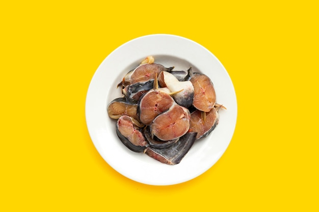 Pezzi tagliati pesce gatto nel piatto su sfondo giallo.