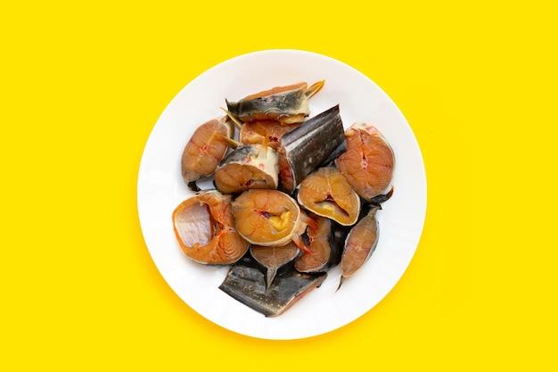 Pezzi tagliati pesce gatto in piatto bianco su sfondo giallo.