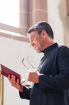 Sacerdote cattolico leggendo la bibbia in chiesa