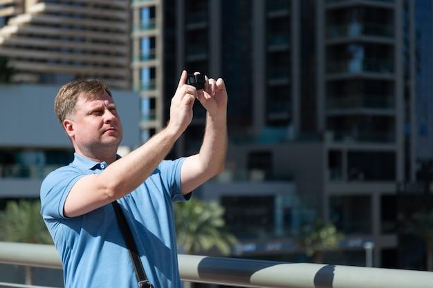 Uomo adulto caucasico le riprese di una grande città turistica su una mini videocamera.