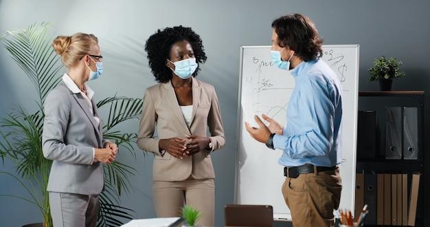Femmine e maschi afroamericani caucasici nelle mascherine mediche che parlano e nel brainstorming. concetto di corona pandemica. uomo d'affari di razza mista e donne d'affari in ufficio. conversazione multietnica dell'uomo e della donna.