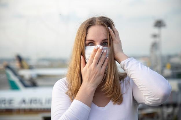 Donna caucasica del passeggero aereo in una maschera medica respiratoria che guarda la telecamera con una faccia spaventata