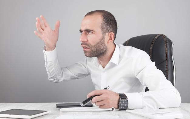 Uomo d'affari arrabbiato caucasico in ufficio.