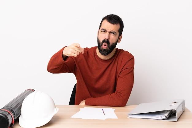Uomo caucasico dell'architetto con la barba in un tavolo frustrato e che indica la parte anteriore.