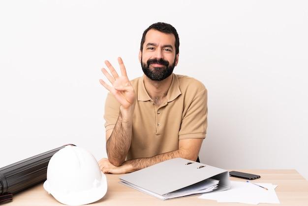 Uomo caucasico dell'architetto con la barba in un tavolo felice e contando quattro con le dita.