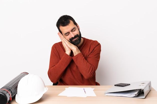 Uomo caucasico dell'architetto con la barba in una tabella che fa gesto di sonno