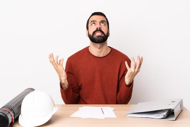 Uomo caucasico dell'architetto con la barba in una tabella ha sottolineato sopraffatto.