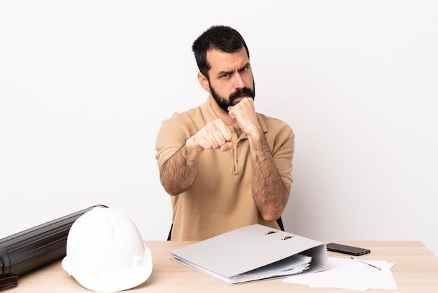Uomo caucasico dell'architetto con la barba in una tabella con il gesto di combattimento