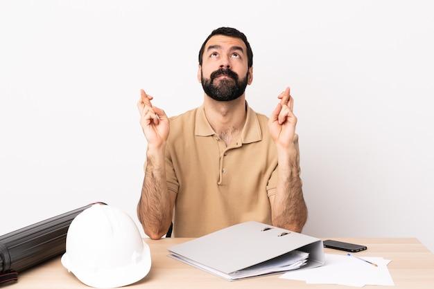 Uomo architetto caucasico con la barba in un tavolo con le dita incrociate e augurando il meglio.