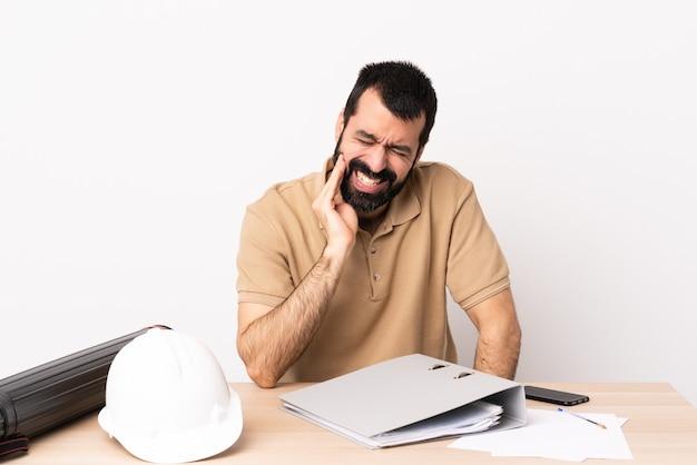 Uomo caucasico dell'architetto con la barba in una tabella con il mal di denti.
