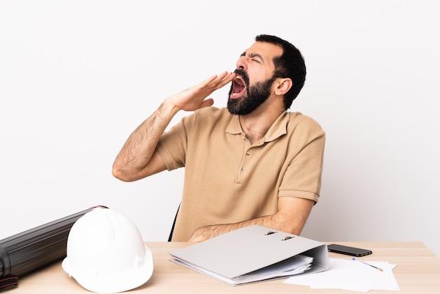 Uomo caucasico dell'architetto con la barba in una tabella che sbadiglia e che copre bocca spalancata di mano