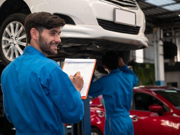 Meccanico caucasico in appunti uniforme della tenuta dell'ordine di servizio che lavora nel garage. lista di controllo dei tecnici per la riparazione di una macchina in garage.