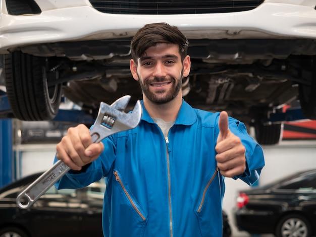 Meccanico caucasico in chiavi della tenuta uniforme e mostrando i pollici in su nel garage. riparazione, servizio auto e concetto di manutenzione