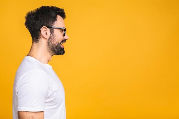 Uomo barbuto caucasico in casual e occhiali isolati su sfondo giallo vista profilo laterale viso, copia spazio per il testo pubblicitario