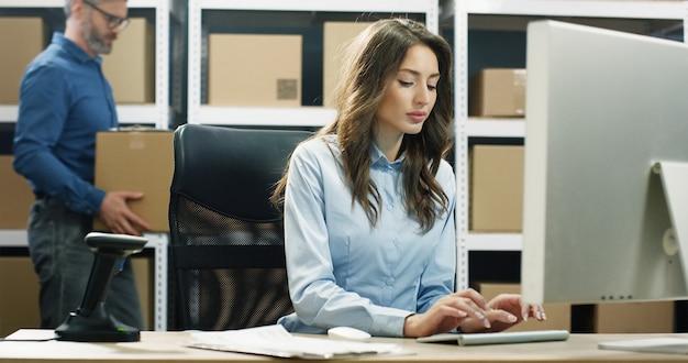 Bella lavoratrice postale caucasica che lavora al computer nell'ufficio di consegna della posta e che scrive sulla tastiera.