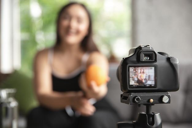Blogger caucasica, la donna fa vlog come fare una dieta e perdere peso, essere positiva per il corpo, mangiare sano. usando la videocamera che registra le sue ricette organiche e gustose. influencer dello stile di vita, concetto di benessere.