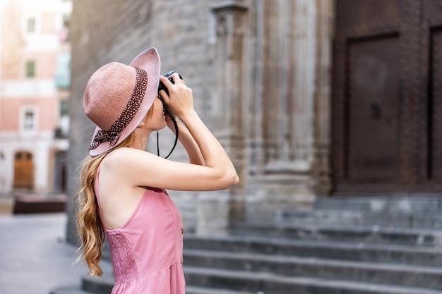 Una bella turista bionda caucasica che indossa un cappello per scattare foto della città
