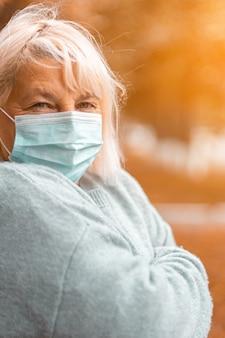 Donna bionda caucasica di 50 anni in un maglione caldo accogliente e una maschera medica protettiva guardando la telecamera in un parco in autunno