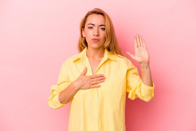 Donna bionda caucasica isolata su sfondo rosa prestando giuramento, mettendo la mano sul petto.