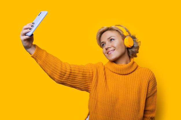 Donna bionda caucasica che fa un ritratto di se stessa mentre ascolta la musica
