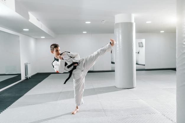 Ragazzo caucasico in dobok che dà dei calci nella posa di dollyo-chagi. taekwondo concetto di formazione.