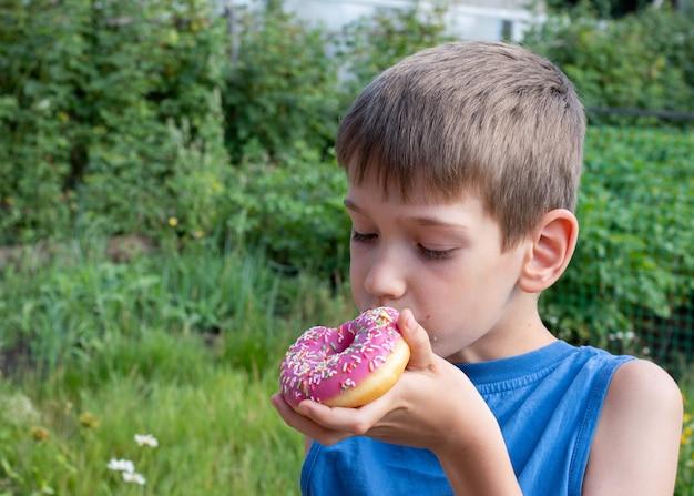 Il ragazzo caucasico mangia la ciambella rosa. bambino tiene un dolce trattamento nel parco.