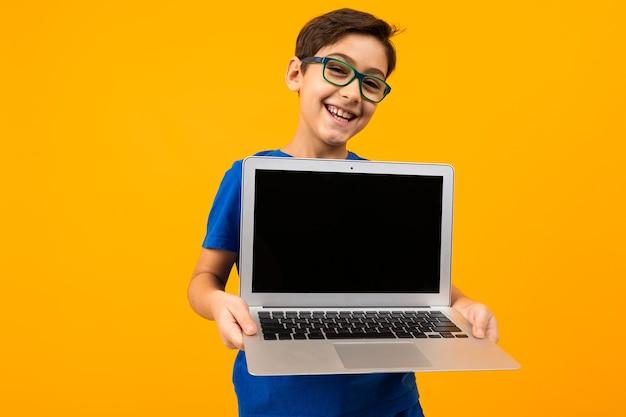 Il ragazzo caucasico tiene lo schermo del laptop in avanti con mock up