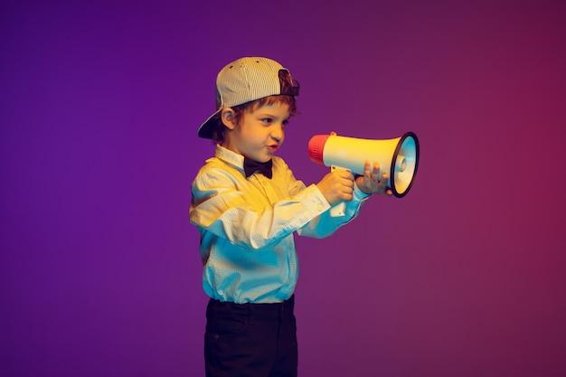 Ritratto di ragazzo caucasico su sfondo studio in luce al neon.