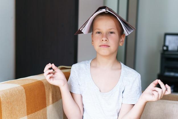 Il ragazzo caucasico seduto sul divano si coprì la testa con un taccuino dalla fatica per risolvere i compiti di un ragazzo