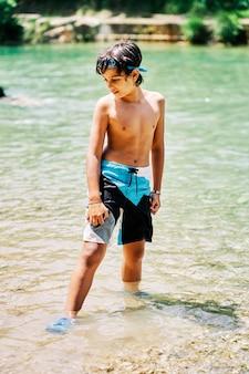 Ragazzo caucasico in costume da bagno e occhiali da sub che guardano giù nell'acqua del fiume in estate