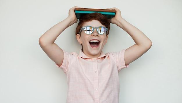 Il ragazzo caucasico con i capelli e gli occhiali rossi sta tenendo un libro sulla sua testa e sorride su un muro bianco