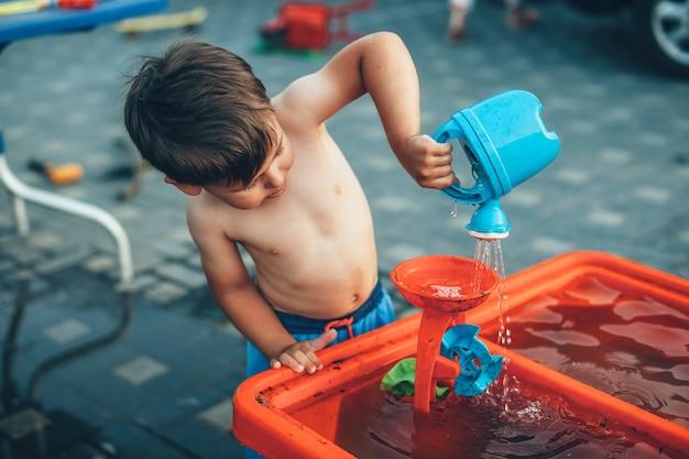 Il ragazzo caucasico senza vestiti sta giocando con i giocattoli di plastica dell'acqua nel cortile durante una giornata estiva
