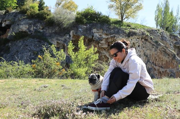 Ragazza bruna caucasica nel campo con il suo cane
