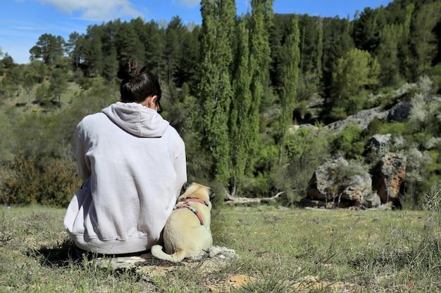 Ragazza bruna caucasica nel campo con il suo cucciolo