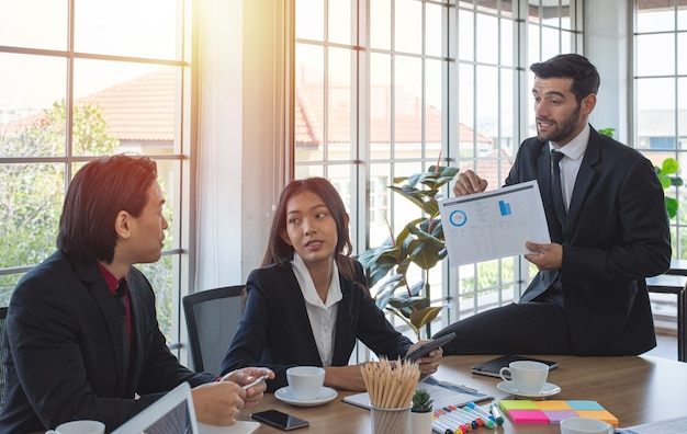 La donna caucasica di affari e il collega asiatico guardano e ascoltano il collega dell'uomo spiegare il grafico nella sala riunioni.