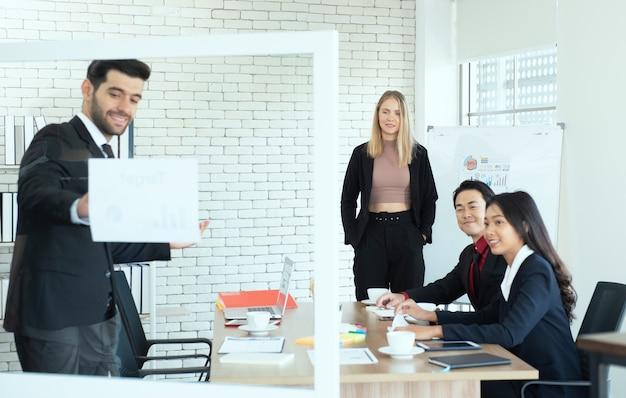 La donna caucasica di affari sta e guarda l'uomo del collega che dà la presentazione con la squadra multietnica.
