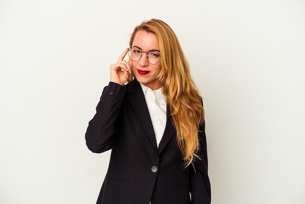 Donna d'affari caucasica che indossa una cuffia wireless isolata su sfondo bianco che punta il tempio con il dito, pensando, concentrata su un compito.