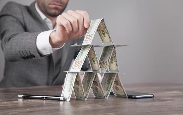 Uomo d'affari caucasico che costruisce piramide finanziaria dai dollari