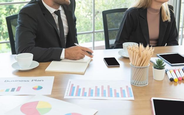 Mano dell'uomo d'affari caucasico che tiene la penna sul tavolo durante la riunione