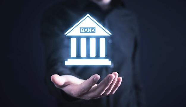 Uomo d'affari caucasico che tiene icona della banca. attività commerciale. finanza