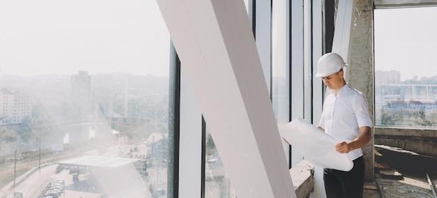 Uomo d'affari caucasico che tiene un piano di costruzione e lo analizza mentre posa vicino a una grande finestra con un casco