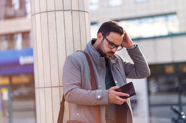 Uomo d'affari caucasico che guarda il portafoglio vuoto