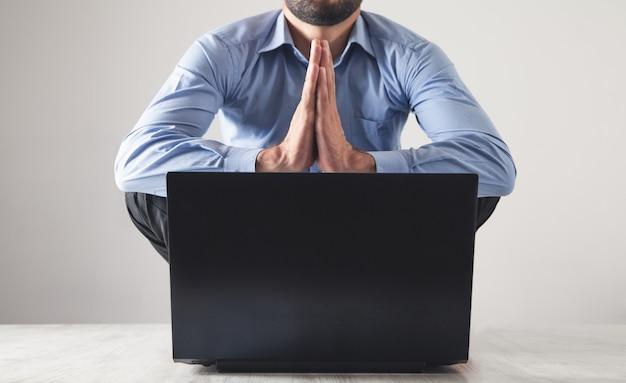 Uomo d'affari caucasico meditando in ufficio. posizione del loto. rilassare