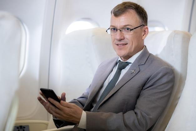 Uomo d'affari caucasico passeggero dell'aereo seduto in un comodo sedile che lavora con lo smartphone