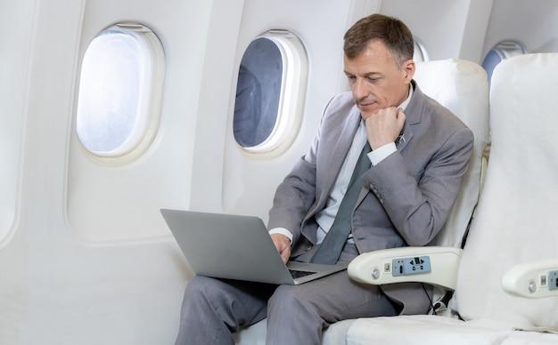 Passeggero d'affari caucasico sull'aereo che lavora con l'area del computer labtop utilizzando la connessione wireless a bordo, uomo d'affari caucasico che controlla il lavoro sulla cabina dell'aereo.