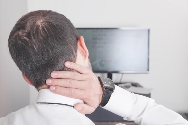 Uomo d'affari caucasico che soffre di dolore al collo in ufficio.