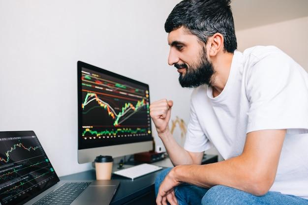 Uomo d'affari caucasico che commercia online, utilizza la tecnologia informatica, esamina il commercio di borsa e analizza
