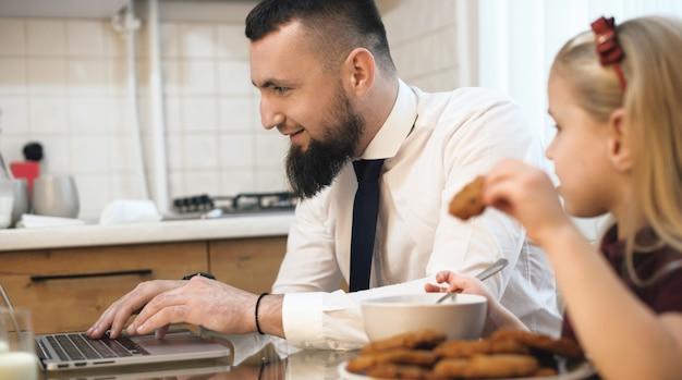 Uomo d'affari caucasico con la barba che lavora al computer e sua figlia che mangia i biscotti allo stesso tavolo